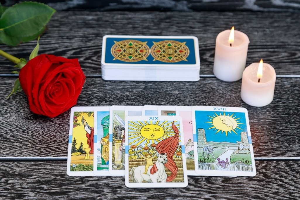 tarot cards scattered on the table a deck of cards burning candles a red rose on a black table t20 roVmJZ min